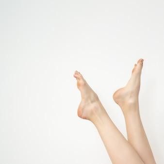 Bei piedi bianchi snelli femminili isolati su fondo bianco