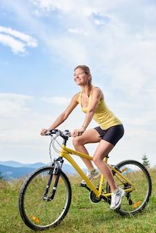 Motociclista femminile che guida sulla bicicletta di montagna gialla