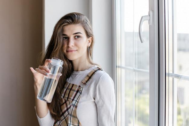 Il blogger femminile beve l'acqua durante la pausa