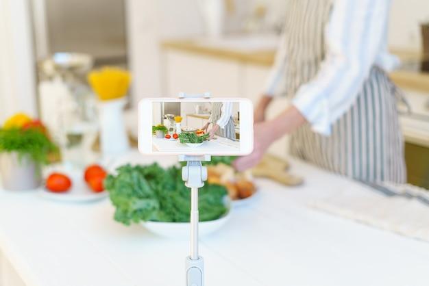 Blogger femminile che registra una ricetta video sul telefono per il blog mentre cucina in cucina a casa