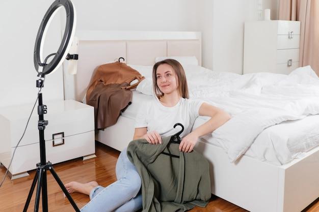 Blogger femminile che registra video vlog su smartphone a casa influencer online in prossimità del letto che sceglie i vestiti, sguardo terreno Foto Premium