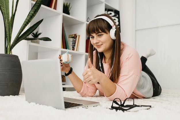 Blogger femminile in streaming a casa con laptop e cuffie