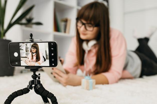 Blogger femminile in streaming con smartphone e cuffie
