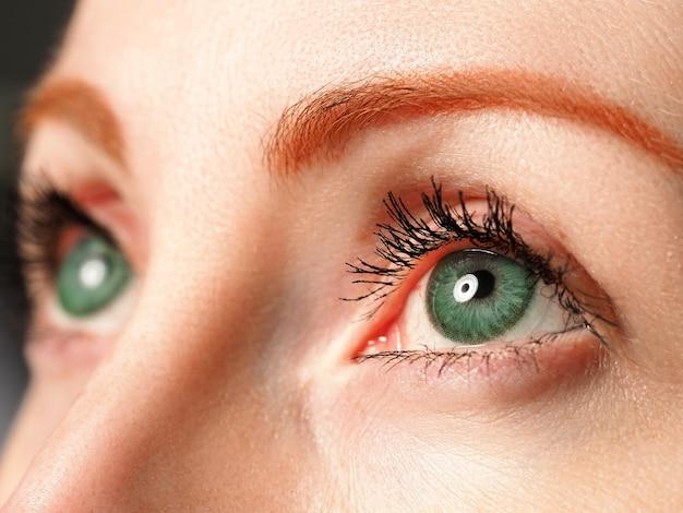 Occhi azzurri femminili colorati in colore verde con primo piano speciale della lente a contatto