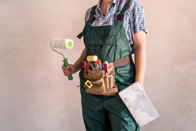 Corpo femminile in uniforme con cintura degli attrezzi e attrezzatura per la pittura