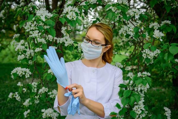 Botanico femmina in camice bianco, mascherina medica e occhiali indossa guanti, lavora con piante in giardino botanico contro l'albero in fiore. ritratto di giovane e bella donna medico, lavorando all'aperto.