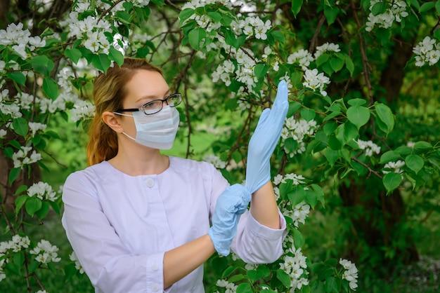 Il botanico femminile in camice bianco, mascherina medica e occhiali mette i guanti