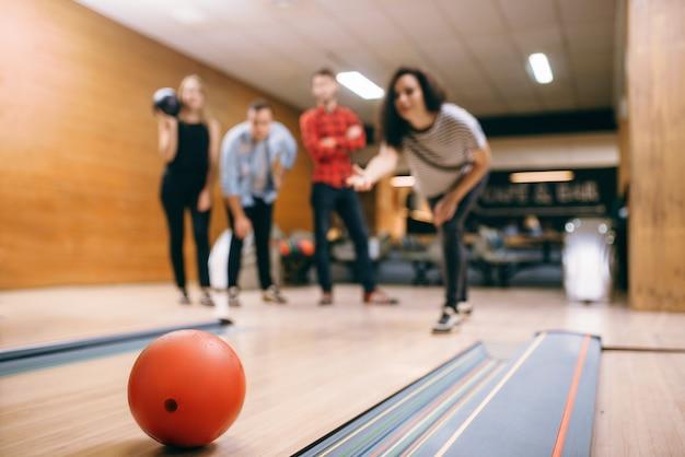 Il giocatore di bocce femminile lancia la palla sulla corsia, colpo di colpo. squadre di bowling che giocano il gioco nel club, tempo libero attivo