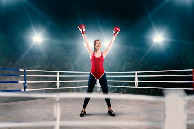 Il pugile femminile in abiti sportivi rossi alza le mani sull'anello