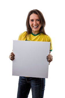 Ventilatore brasiliano femminile che tiene un bordo in bianco, su uno spazio bianco.