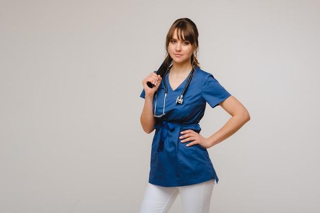 Dottore femminile del brunette che esamina pellicola dei raggi x di tomografia.