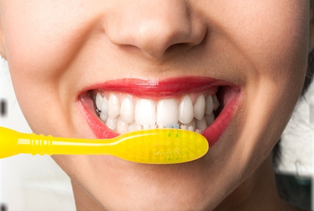 Femmina che lava i denti con la spazzola gialla, primo piano