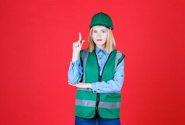 Costruttore femminile in uniforme, casco che indica la parte superiore del dito, che mostra l'offerta promozionale su un muro rosso
