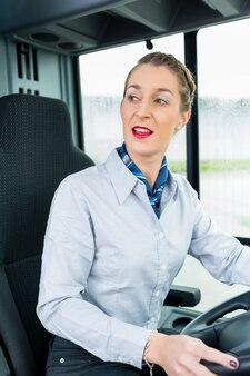 Autista di autobus femminile nel sedile del conducente Foto Premium