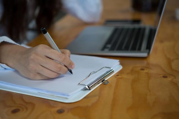 Scrittura femminile dell'uomo d'affari sulla lavagna per appunti