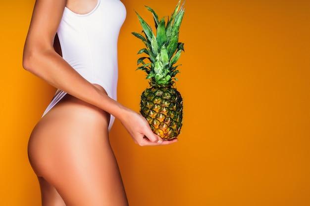 Natiche femminili, culo sexy. giovane donna sportiva che tiene un ananas in sua mano.
