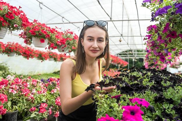 Il compratore femminile sceglie i bei fiori in una serra. stile di vita