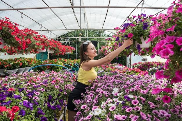 Il compratore femminile sceglie bellissimi fiori in una serra
