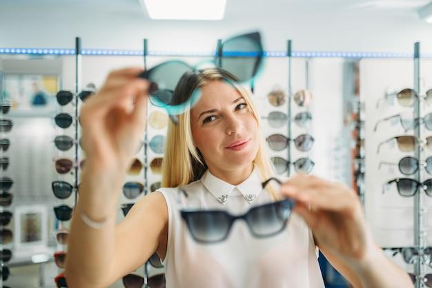 Il compratore femminile sceglie gli occhiali da sole nel negozio di ottica, vetrina con gli occhiali
