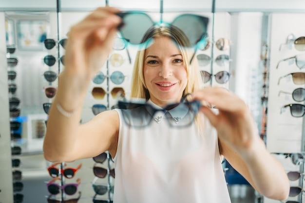 Il compratore femminile sceglie gli occhiali da sole nel negozio di ottica
