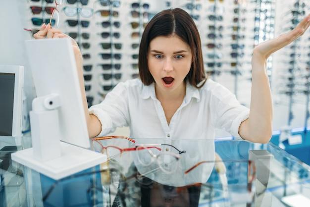 Acquirente femminile sorpreso dall'effetto di occhiali, negozio di ottica, vetrina con occhiali sullo spazio. eyecare professionale nel concetto di negozio di occhiali