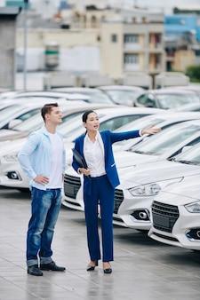 Responsabile di concessionaria auto femminile che mostra le auto al cliente e lo aiuta a scegliere la migliore