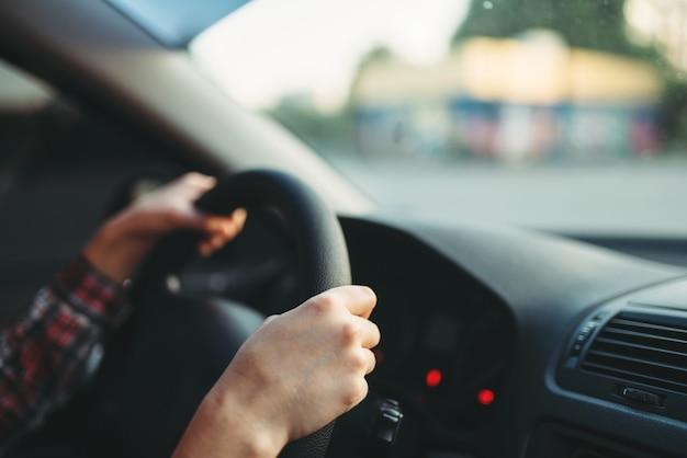 Principiante automobilista femminile aggrappato al volante