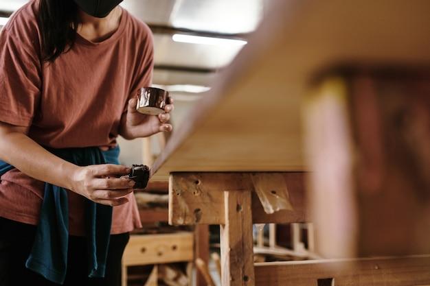 Carpentiere femminile che applica finitura protettiva sul progetto di lavorazione del legno con un pezzo di stoffa
