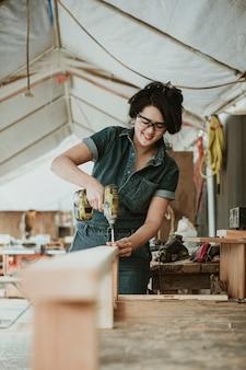 Carpentiere femminile che perfora un legname