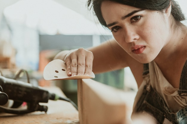 Carpentiere femminile che leviga il legname con un disco abrasivo