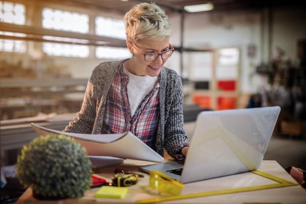 Il carpentiere femminile che utilizza il computer portatile e nell'altra mano che tiene i progetti mentre stanno nell'officina