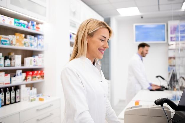 Farmacista caucasico femminile che vende medicinali in farmacia.