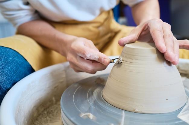 Creatore di ceramica femminile che lavora con il tornio in officina accogliente