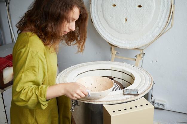 La ceramista tira fuori da un forno dopo la cottura. maestro ceramista che lavora in studio di ceramica. processo di creazione della ceramica.