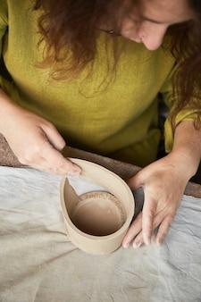 Ceramista femminile che lavora nello studio delle terraglie. le mani del ceramista sporche di argilla. processo di creazione della ceramica. il maestro ceramista lavora nel suo studio