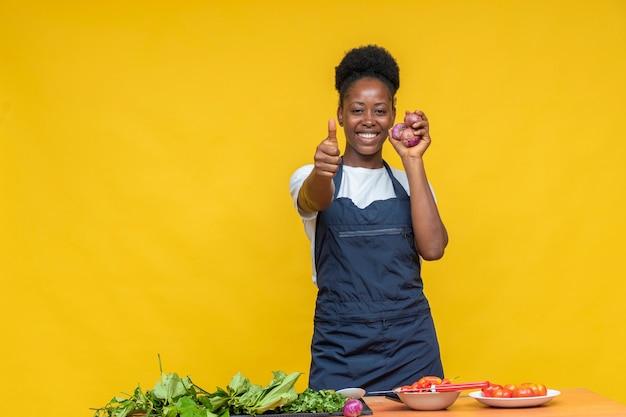 Cuoco unico femminile che tiene alcune cipolle e fa un pollice in alto con un sorriso sul viso