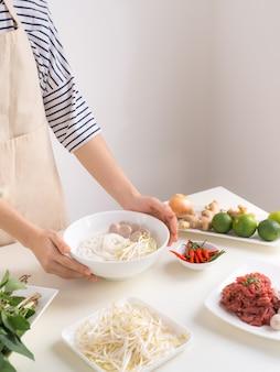 Lo chef femmina prepara la zuppa tradizionale vietnamita pho bo con erbe, carne, spaghetti di riso
