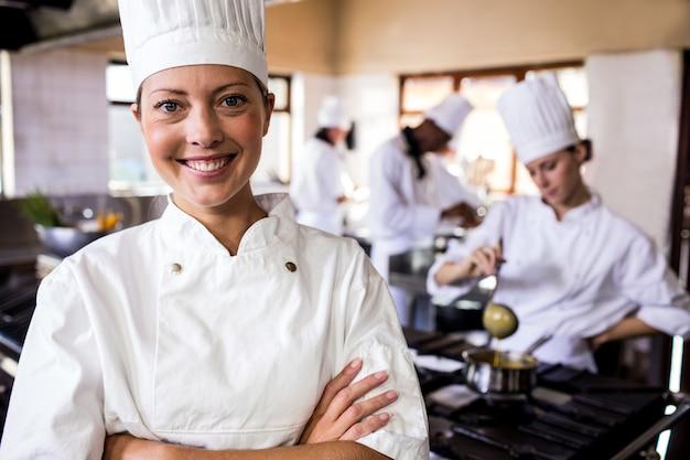 Il cuoco unico femminile che sta con le armi ha attraversato in cucina