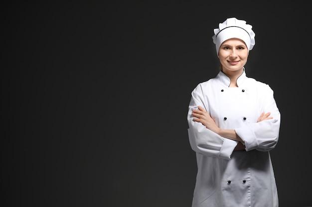 Cuoco unico femminile in uniforme sul nero