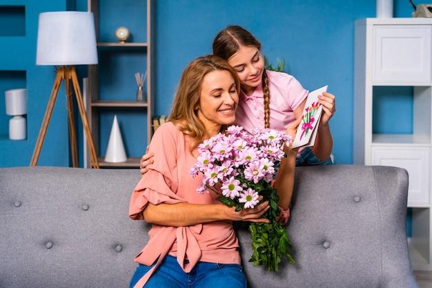 Bambina che presenta fiori a sua madre a casa, momenti felici della vita domestica