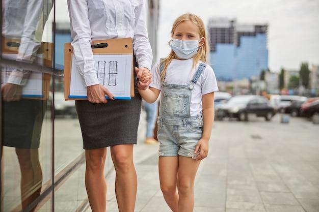 Bambina che indossa una maschera protettiva che cammina per la strada della città con sua madre adulta