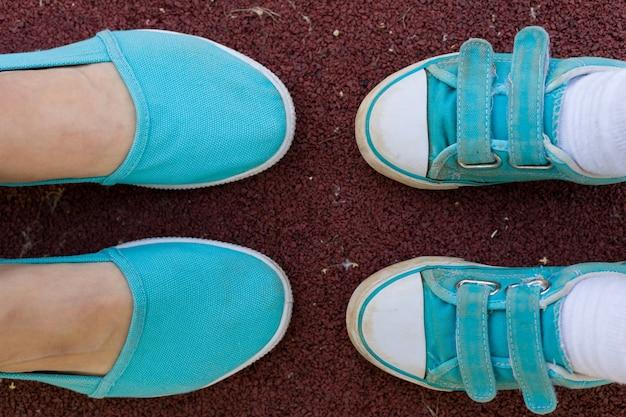 Piedi femminili e infantili in scarpe sportive turchesi a terra in un parco