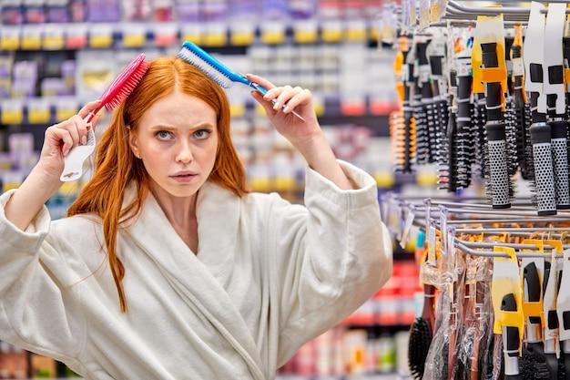 Donna che sceglie un nuovo pettine in negozio, cerca di spazzolare i capelli lunghi usandoli, pensa, confronta i prodotti