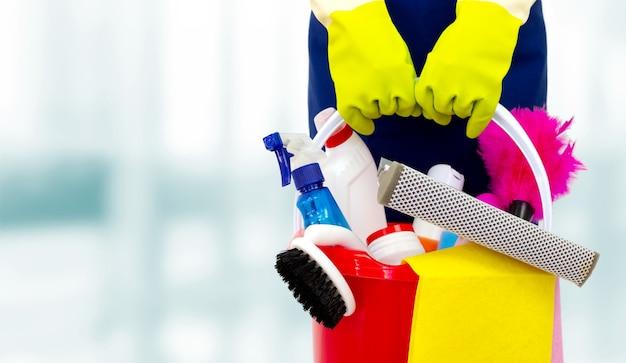Pulitore femminile che tiene un secchio con prodotti per la pulizia. servizio di pulizia concettuale