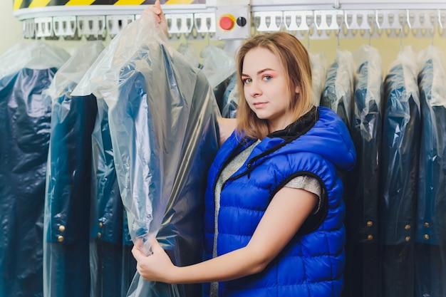 Detergente femminile in lavanderia o lavaggio a secco in tessuto accanto a vestiti puliti in sacche porta abiti.