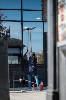 Una donna addetta al servizio di pulizia lava le grandi finestre anteriori di un edificio in una giornata di sole. donna in maschera medica protettiva. la seconda ondata della pandemia di covid19