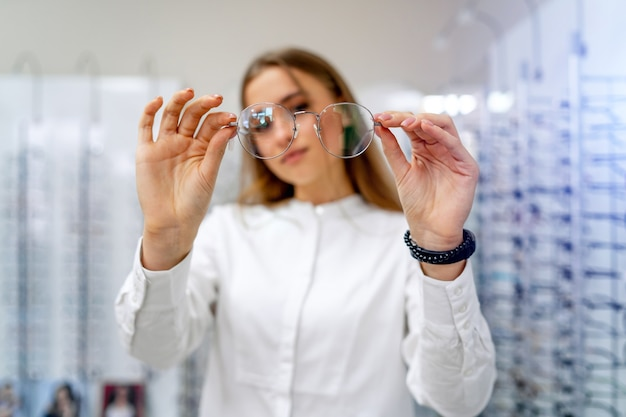 Il cliente o l'ottico femminile sta levandosi in piedi con gli occhiali grezzi