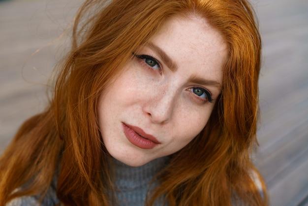Primo piano femminile ritratto caucasico dai capelli rossi carino giovane donna con lentiggini e occhi verdi