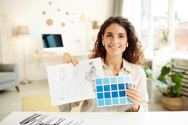 Designer di abiti femminili che mostra schizzi e tavolozza di colori blu