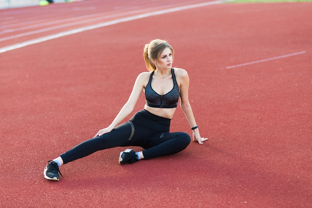 Un'allenatrice dai capelli scuri è in piedi sulla pista rossa dello stadio, vestita con una divisa sportiva.